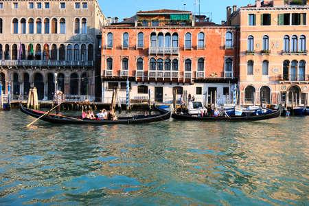 Venice, Italy - September 18, 2020: Gondoliers take tourists on his gondolas on Grand Canal. Venice during coronavirus pandemics.