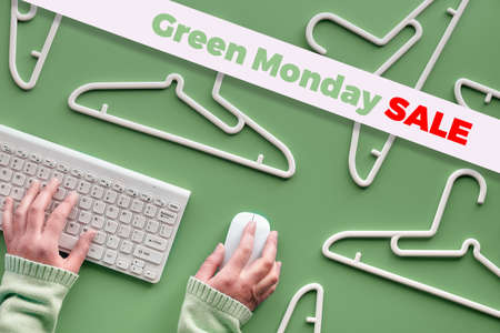 Green Monday sale text on green background with hands on keyboard and computer mouse. White plastic hangers. Design for promotion of winter, Christmas and end of year sale.