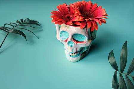 Skull in face mask with coral color gerbera flowers. Dia de los Muertos, creative surreal modern design..