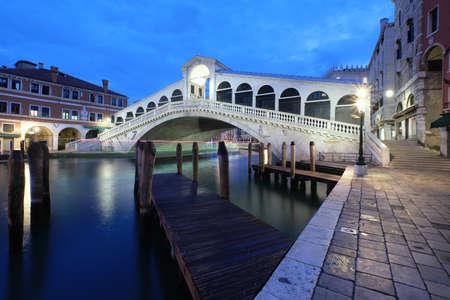 Illuminated Rialto bridge on The Grand Canal in Venice, Italy early in the morning.