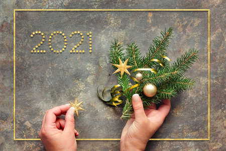 Text 2021. Happy New Year Hands holding decorated fir twigs and star. Golden trinkets, baubles and stars. Flat lay on dark textured wood.