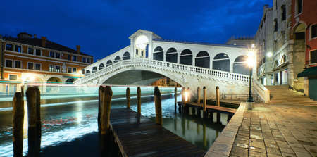 Illuminated Rialto bridge on The Grand Canal in Venice, Italy at night. Panoramic image. Tracers from boat lights under the bridge.
