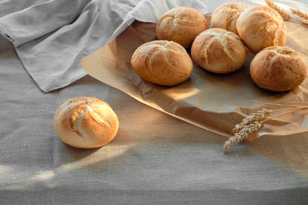 Crusty round bread rolls, known as Kaiser or Vienna rolls on table covered with linen table cloth. Textile towel and wheat ears.