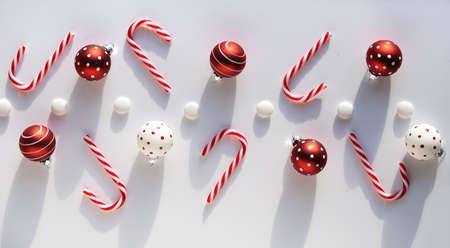 Panoramic Christmas background, top view om geometric arrangement with candy canes, red and white trinkets with magic mashroom dots and candy buttons on white table.
