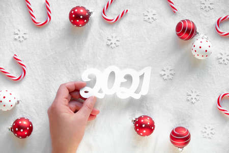 New Year 2021 background. Top view of female hand holding paper number. Red and white trinkets with dots, snowflakes and candy canes on white textile background.