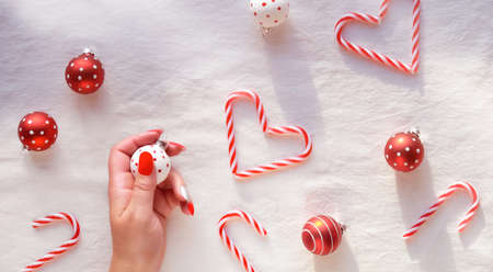 Panoramic Christmas background, top view with female hands holding Xmas bauble. Heart shapes made from candy canes, red and white trinkets with dots on white textile background.