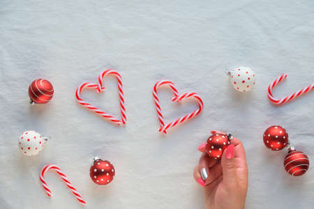 Christmas background, top view with female hands holding Xmas bauble. Heart shapes made from candy canes, red and white trinkets with dots on white textile background.