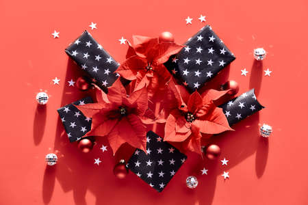 Monochrome Christmas background in red and silver with shadows, top view. Poinsettia and Xmas decorations, disco balls and gift boxes.