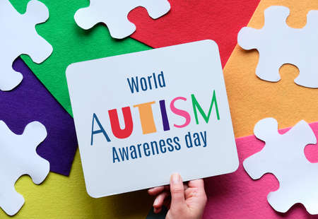 Hand holding caption for World Autism spectrum disorder Awareness Day on multicolor felt layered background with jigsaw pieces