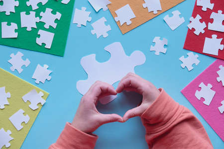 Hands show heart sign. Flat lay, top view on creative arrangement. Jigsaw puzzle elements and multicolor felt sheets on blue background. 版權商用圖片