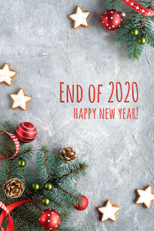 Text End of 2020, Happy New Year. Zero Waste Christmas background. Xmas flat lay, corner arrangement. Natural fir twigs, ribbons, stripy candy canes, pine cones and red trinkets.