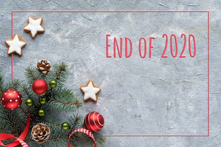 Text End of 2020. Zero Waste Christmas background. Xmas flat lay, top view, corner arrangement of natural fir twigs, dry oranges, stripy candy canes, pine cones and red trinkets. Imagens