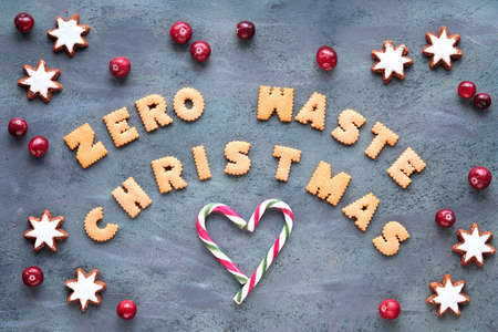 Text Zero Waste Christmas made from cookies. Xmas top view. Minimal design with candy canes, star cookies and fresh cranberry, Natural Christmas decorations on grey aged background. 版權商用圖片 - 167039231