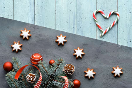 Zero Waste Christmas background. Xmas flat lay with heart from stripy candy canes. Fir twigs, ribbons, cones, star cookies and red balls. Dark light split wooden background. Happy New Year 版權商用圖片 - 167038646