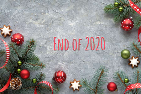 Text End of 2020. Grey textured Zero Waste Christmas background. Xmas flat lay, top view, panoramic banner design. Frame with fir twigs, dry oranges, candy canes, cones, star cookies and red trinkets.