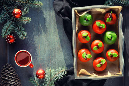 Marzipan sponge apples. Christmas dessert with cup of tea, fir twigs, green candle, pine cone, baubles. Top view on in rustic wooden tray on textile towel.
