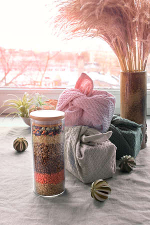 Zero waste gifts, jars of food ingredients, tea leaves, boxes packed in towels furoshiki style. Glass jar with layered beans and cereals. Sustainable presents on neutral linen tablecloth by window.