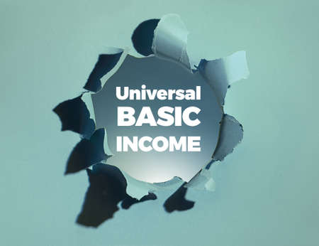 Text Universal Basic Income in white bold letters appearing from paper hole. Blue paper background with torn hole. Unconditional basic income delivered to all citizens without requirement to work.