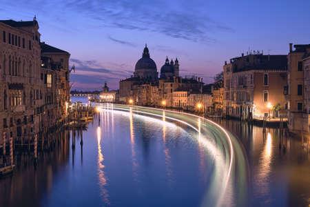 Romantic Venice at night. Cityscape image of Grand Canal in Venice, with Santa Maria della Salute Basilica reflected in calm sea. Lights of passenger boat on the water.