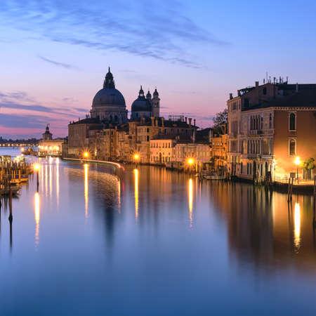 Romantic Venice at night. Cityscape image of Grand Canal in Venice, with Santa Maria della Salute Basilica reflected in calm sea. Lights of passenger boat on the water. Foto de archivo