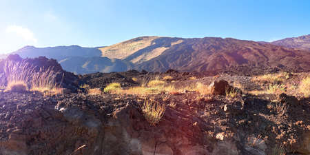 Mount Etna in Sicily near Catania, Tallest active Europe volcano in Italy. Panoramic wide view of the active volcano Etna, ash and lava, traces of volcanic activity. Sunny day, sun flare. 版權商用圖片