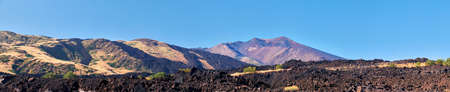 Mount Etna in Sicily, Tallest active Europe volcano in Italy. Panoramic wide view of the active volcano Etna, volcanic ash and lava fields, traces of volcanic activity.