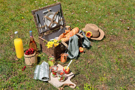 Zero waste picnic al fresco. Vintage picnic basket, hamper with baguette and homemade lemonade outdoors on a grass, Glass jars with cheese, mozzarella, tomatoes, cherries, vine and flowers.