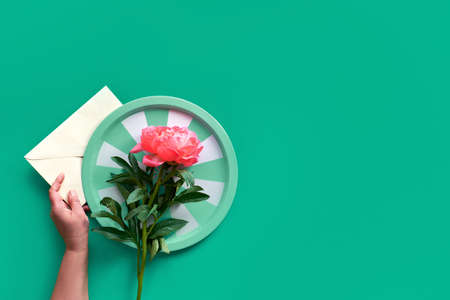 Hands holding tray with single pink peony flower over paper envelope on green background with copy-space. Trendy casual natural eco friendly flat lay. Summer birthday or Mother's day greeting card design.