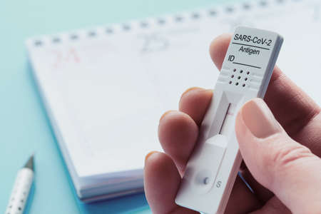 Week planner, chnelltest, rapid corona test in German language. Week planner calendar on blue table. Test-to-go concept.