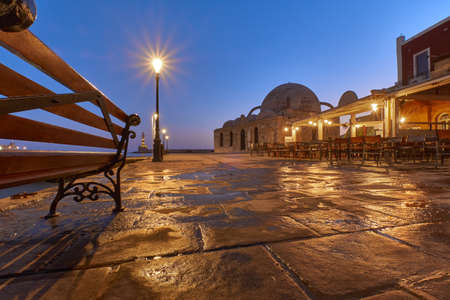 old venetian port Xania Creta Greece towards to the lighthouse in twilight, a bench restaurants ancient lamps and the Mosque K k Hasan in the foreground
