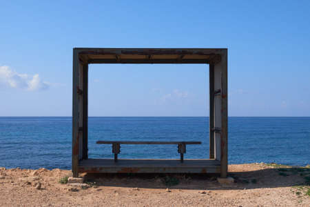 a wooden frame as sun shield with an empty bench towards th sea Paphos Cyprus