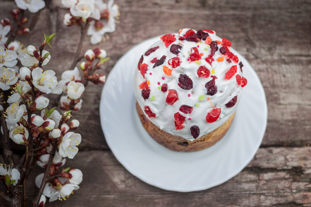 Beautiful Easter cake stands on a wooden surface, in the background the blooming apricot.