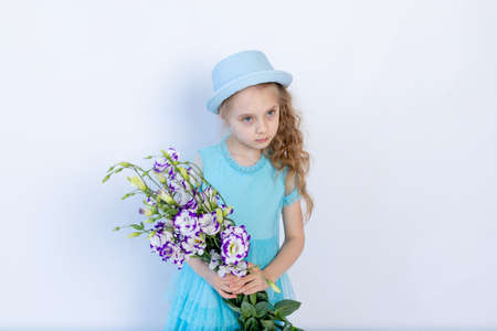 sad girl 5-6 years old in a blue dress and hat on a white isolated background holding a bouquet of flowers, space for text