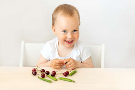 baby boy 2 years old sitting at a table on a white isolated background and eating berries and peas, baby food concept, place for text