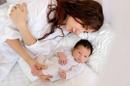 母亲在床上躺在床上用刚出生的婴儿在白色背景上,拥抱她的儿子7天,家庭日,母亲的爱和关怀。
