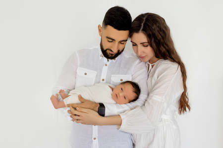 parents hold a newborn baby on a white background, mom and dad hold their son for 7 days, family day.