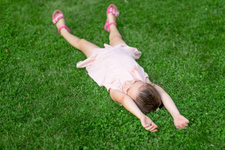 a 5-6-year-old girl lies on her back in the Park on the grass, happy childhood, child's day
