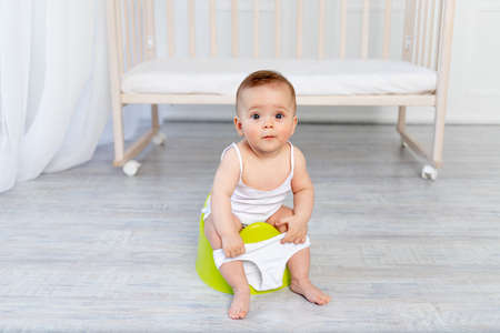 small baby girl 8 months old sitting on a potty, baby toilet, place for text