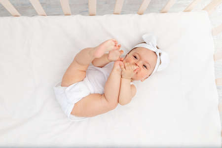 baby girl 6 months old lies in a crib in the nursery with white clothes on her back and laughs, looks at the camera, baby's morning, baby products concept Standard-Bild