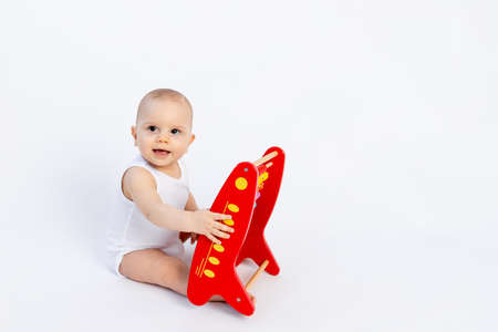 child playing with bills on a white background, early development, up to a year, space for text Foto de archivo