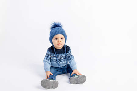 Baby 8 months old boy sitting on a white isolated background in warm winter clothes and a hat, children's fashion, advertising children's clothing, space for text