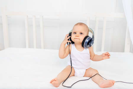 small baby boy 8 months old sitting on the bed in the children's room with headphones and listening to music, place for text