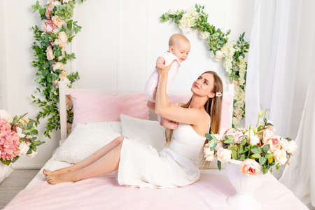 a young beautiful mother with a 6-month-old daughter in her arms sits on a white bed in flowers and hugs her, a place for text