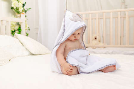 baby boy 8 months old sitting on a white bed in a white towel after bathing in the bathroom at home, place for text Stockfoto