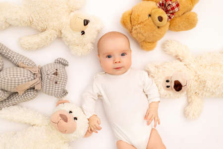 portrait of a child on a white background with plush bear toys. Baby 6 months among toys. Space for text Reklamní fotografie