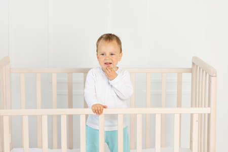 a small boy 2 years old is crying in the crib, parents do not approach the crying baby Reklamní fotografie