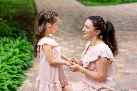 Happy mother and daughter 5-6 years old walk in the Park in the summer, mother talks to her daughter, the concept of a happy family, the relationship of mother and child