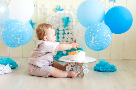 baby boy 1 year in a photo Studio with a cake and balloons, Birthday of a child 1 year, baby eats cake Archivio Fotografico