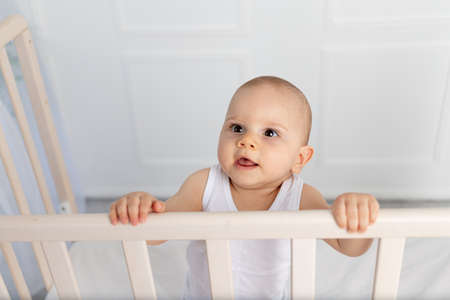 portrait of a smiling baby boy 8 months old standing in a crib in a children's room in white clothes and looking away, morning baby, baby products concept