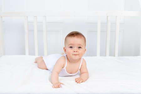 smiling baby girl 6 months old lying on the bed in the nursery on her stomach and looking at the camera, morning baby, baby products concept Standard-Bild